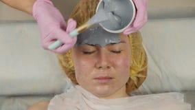 Schoonheidsspecialist die moddermasker aanvragen vrouwengezicht in de kuuroordsalon gezichtsverjongingsprocedure, kuuroordbehande stock videobeelden