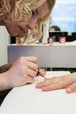 Schoonheidsspecialist die nagellak toepassen Royalty-vrije Stock Foto's