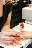 Schoonheidsspecialist die nagellak toepassen Stock Fotografie