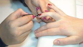 Schoonheidsspecialist die Poolse spijkers toepassen op vrouwenspijkers stock footage