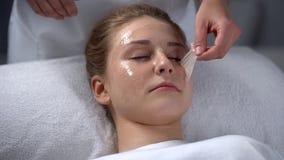 Schoonheidsspecialist het verwijderen blijft van masker van meisjesgezicht, diep het schoonmaken van poriën stock foto's