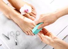 Schoonheidsspecialist oppoetsende spijkers, pedicure royalty-vrije stock afbeelding