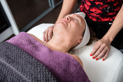 Schoonheidsspecialist Standing By Customer die Behandeling in Salon ondergaan stock fotografie