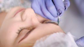Schoonheidsspecialist van de close-up de hoge hoek bij het werk wenkbrauw permanente make-up of het microblading bij schoonheidss stock videobeelden