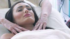 Schoonheidsspecialist wat betreft vlotte huid op hals van gezonde vrouw stock footage