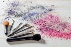 Schoonheidsstilleven met make-upborstels en verpletterde oogschaduwkleuren Stock Afbeeldingen