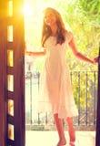 Schoonheidstiener in de witte kleding die zich in de open deur bevinden royalty-vrije stock fotografie