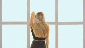 Schoonheidstiener het dansen Tegen de achtergrond van een venster in de vorm van een kooi, kubussen en vierkanten Blije tiener stock footage