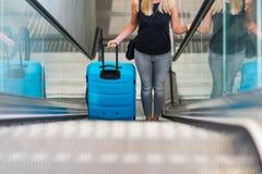 Schoonheidsvrouw die en haar bagage op roltrap reizen houden stock afbeeldingen