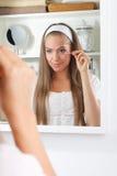 Schoonheidsvrouw die haar make-up in mirrow bevestigen royalty-vrije stock foto's