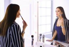 Schoonheidsvrouw die make-up toepassen Mooi meisje die in de spiegel kijken en schoonheidsmiddel met een grote borstel toepassen stock fotografie