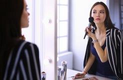 Schoonheidsvrouw die make-up toepassen Mooi meisje die in de spiegel kijken en schoonheidsmiddel met een grote borstel toepassen royalty-vrije stock afbeeldingen