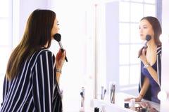 Schoonheidsvrouw die make-up toepassen Mooi meisje die in de spiegel kijken en schoonheidsmiddel met een grote borstel toepassen royalty-vrije stock foto