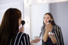 Schoonheidsvrouw die make-up toepassen Mooi meisje die in de spiegel kijken en schoonheidsmiddel met een grote borstel toepassen stock foto's