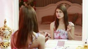 Schoonheidsvrouw die make-up toepassen Mooi meisje die in de spiegel kijken stock video