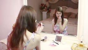 Schoonheidsvrouw die make-up toepassen Mooi meisje die in de spiegel kijken stock videobeelden
