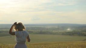 Schoonheidsvrouw die op tarwegebied lopen over zonsonderganghemel Het concept van de vrijheid Gelukkige vrouw in openlucht Het ge stock video