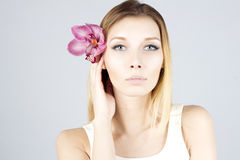 Schoonheidsvrouw met roze bloem in haar Duidelijke en verse huid Het Gezicht van de schoonheid Royalty-vrije Stock Afbeeldingen