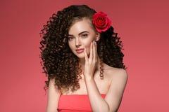 Schoonheidsvrouw met roze bloem mooie krullende haar en lippen stock afbeelding