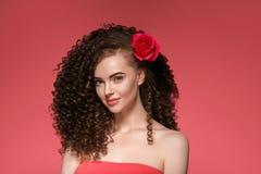 Schoonheidsvrouw met roze bloem mooie krullende haar en lippen stock afbeeldingen