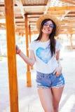 Schoonheidsvrouw in zonnebril en hoed op een pool die zich dichtbij chaise zitkamer in de zomertijd bevinden stock foto