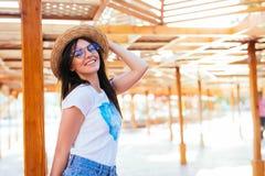 Schoonheidsvrouw in zonnebril en hoed op een pool die zich dichtbij chaise zitkamer in de zomertijd bevinden stock fotografie