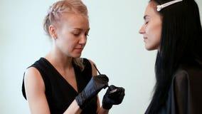 Schoonheidszaal de schoonheidsspecialist in de zwarte rubberingrediënten van handschoenenmengelingen, de meester bereidt de verf  stock video