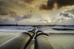 Schoonheidszonsopgang bij de kustlijn concrete drainagepijp bij het strand donkere en dramatische wolken met straal van licht Stock Afbeelding