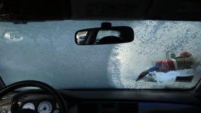 Schoonmakend autoraam met een ijsschraper stock videobeelden