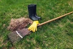 Schoonmakend gazon van droog gras met een hark in de lentetuin Hoop van gras met laarzen en hulpmiddel royalty-vrije stock afbeelding