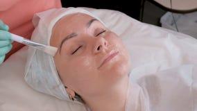 Schoonmakend masker voor het gezicht van een vrouw in de schoonheidssalon De artsenschoonheidsspecialist zet bevochtigend gel op  royalty-vrije stock afbeeldingen