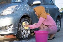 Schoonmakende de autobanden van de Hijabvrouw bij in openlucht gebied stock foto's