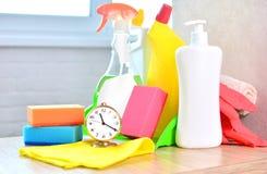 Schoonmakende de dienstachtergrond met huishoudenchemische producten en klok Concept netheid en versheid in het huis royalty-vrije stock foto's