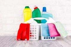 Schoonmakende hulpmiddelen - vloeistof, deeg, gel in plastic containers Borstel, spons, microfiber servet en rode rubberhandschoe stock foto's