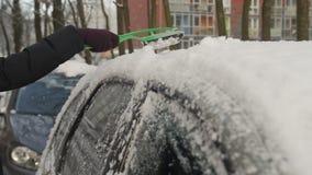 Schoonmakende sneeuw van de auto stock footage