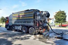 Schoonmakende vrachtwagenpompen uit het waterafvoerkanaal royalty-vrije stock afbeeldingen