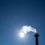 Schoorsteen uitputtende stoom in blauwe hemel Stock Afbeelding