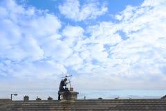 Schoorsteenveger op het werk aangaande het dak Stock Foto's