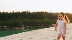 Schoot de Steadicam langzame motie: vrolijk onbezorgd meisje drie jaar die in het zand lopen Tegen de achtergrond van stock footage