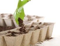 Schop die Grond plaatst in de Milieuvriendelijke Potten van het Compost Royalty-vrije Stock Fotografie