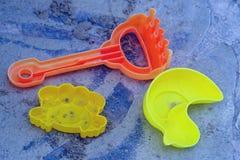 Schop en hark, het onontbeerlijke speelgoed op het strand De kleurrijke achtergrond van de de zomervakantie royalty-vrije stock afbeeldingen