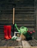 Schop, gieter, hoed, rubberlaarzen, doos van bloemen, handschoenen en tuinhulpmiddelen royalty-vrije stock foto's