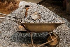 Schop met cementkar en grint zwarte rots op bouwwerf voor achtergrond Bouwbegin met planning, ontwerp, en stock foto