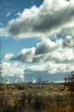 Schornsteine der Fabrik in Abstand mit bewölktem Himmel am Herbst Stockbild