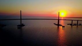schoss Luftbrummen des Meerblicks 4k Frühsommermorgensonnenaufgang über Stahlbrücke der enormen Landstraßenstraße über ruhigem ti stock video
