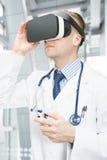 Schoss zuhause von männlichem Doktor, der VR-Gläser trägt Stockfotografie