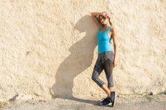 Schot die van geschikte agent tegen een muur zich in openlucht bevinden Het sportieve vrouw ontspannen na het runnen van oefening royalty-vrije stock foto's