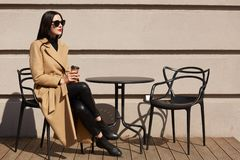 Schot die van vrouw modieuze laag dragen die ontbijt in comfortabele straat openluchtkoffie hebben en koffie van document mok dri royalty-vrije stock afbeeldingen