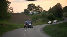 Schot door achterglas op de landweg en de concurrerende fietsers stock videobeelden