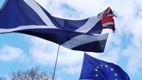 Schot, Union Jack en de Europese Unie markeren het vliegen voor wolken en blauwe hemel, Westminster, Londen stock videobeelden